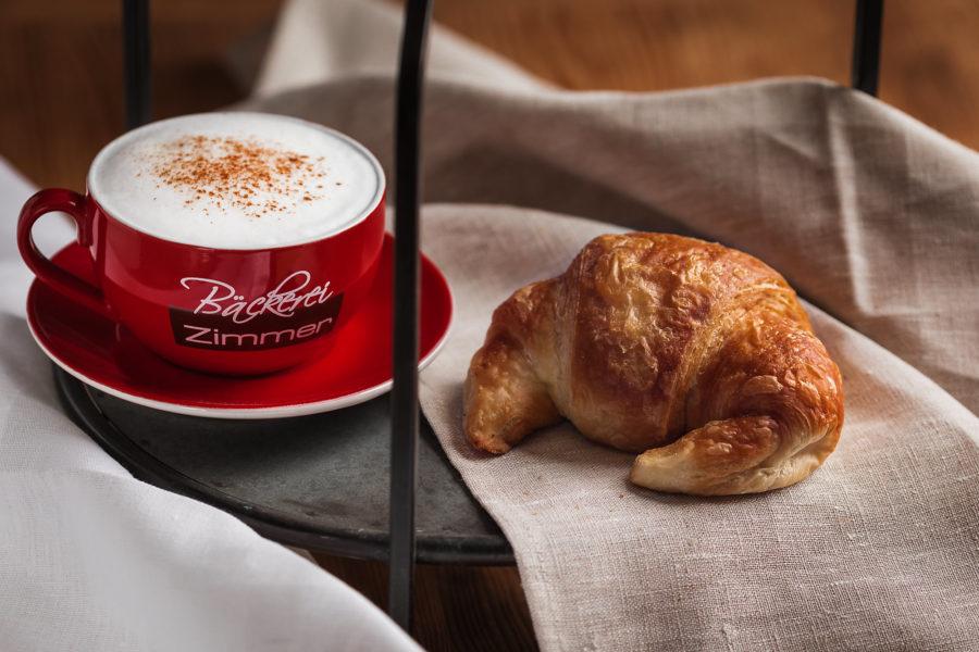 Leckerer Cappuccino und ein Croissant, serviert auf einem Tablett mit einem Tuch.