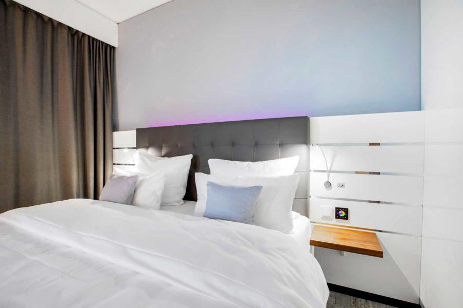 Gemütliches Bett, in einem hellen Hotelzimmer des Nordport Plaza in Hamburg.