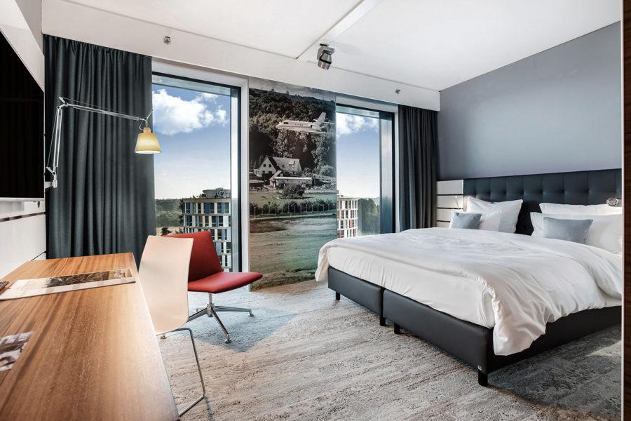 Ein gemütliches Hotelzimmer mit 2 bodentiefen Fenstern, einem großen Bett und einem Schreibtisch, mit Blick auf den Flughafen Hamburg.