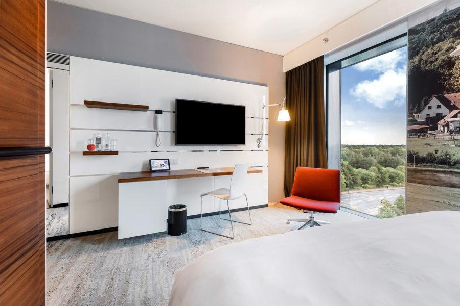 Gemütliches Hotelzimmer mit Blick auf den Schreibtisch und ein bodentiefes Fenster.