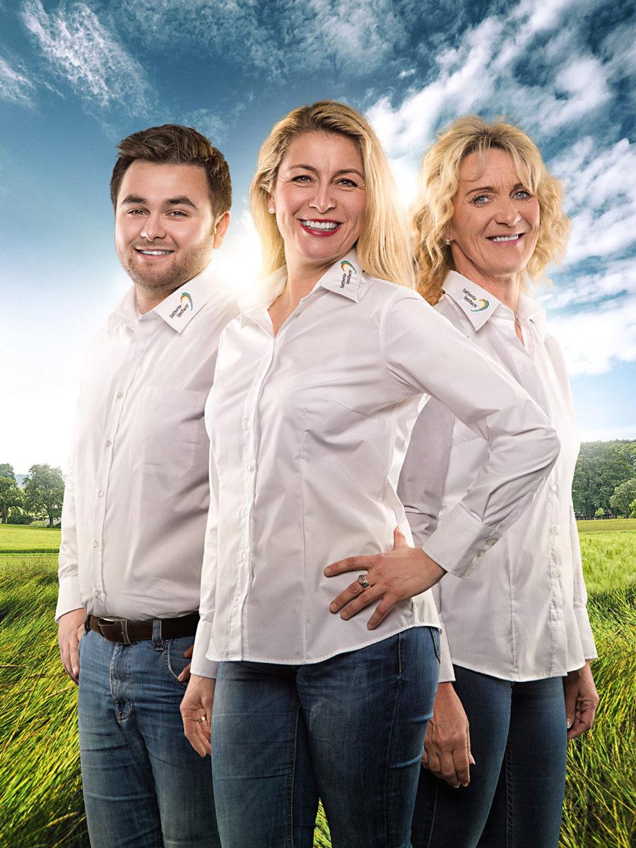 3 Mitarbeiter der Stadtwerke Geesthacht, freundlich lächelnd nebeneinander stehend vor einer Wiese.