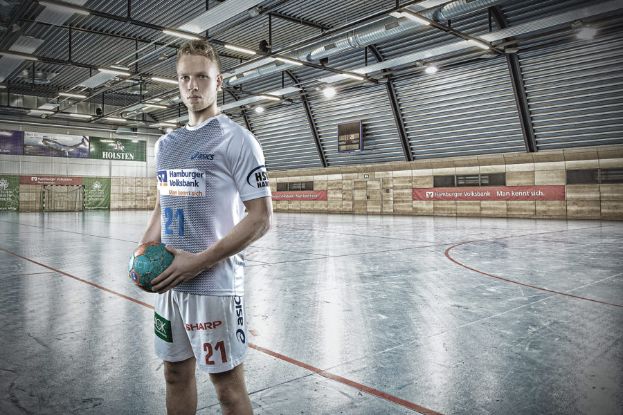 Junger Handballspieler des HSV in einer Halle mit einem Ball in der Hand.