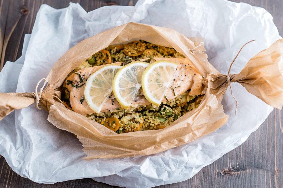 Frischer Lachs aus dem Ofen, in Backpapier gegart, mit Couscous und Zitrone.