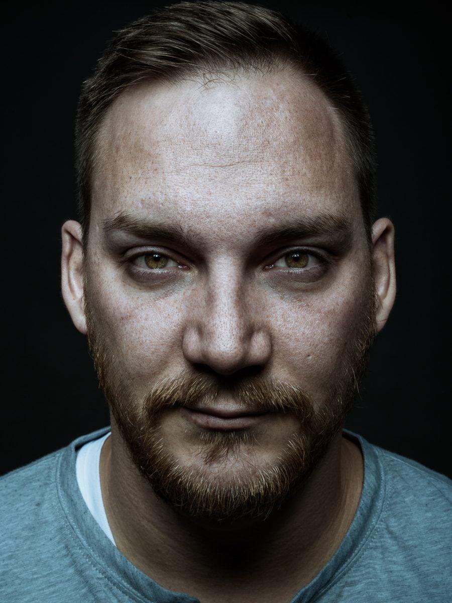 Charakter Portrait eines jungen Mannes, aufgenommen im Fotostudio, vor einem schwarzen Hintergrund.