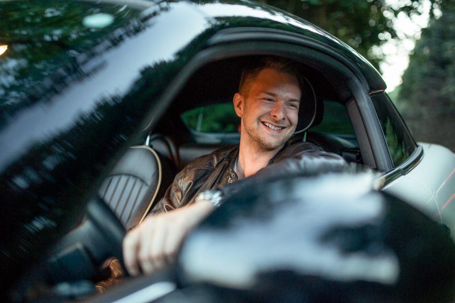Portrait eine Mannes, der in einem Mini Cooper sitzt, mit offener Fensterscheibe und lächelt.
