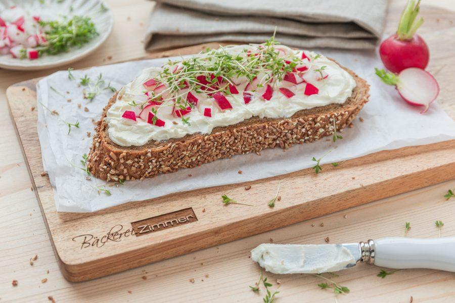 Frische Scheibe Brot mit Frischkäse und Kräutern auf einem Brett.