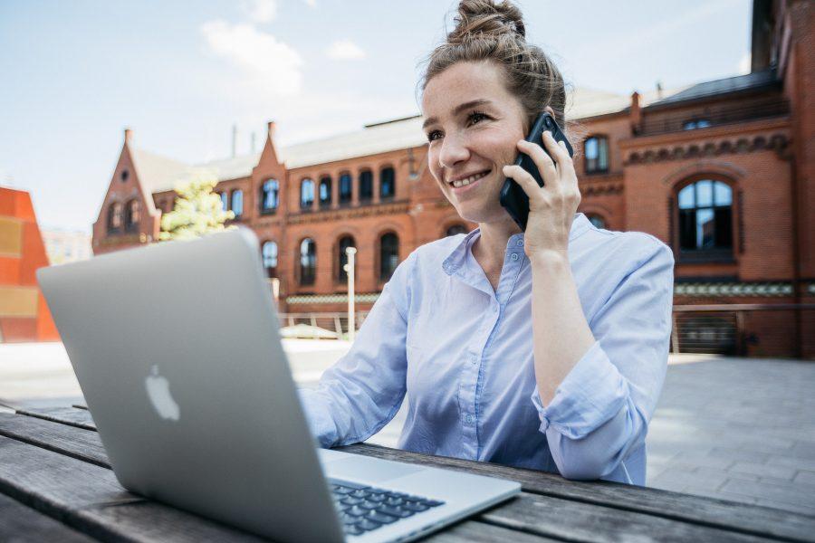 Business Portrait einer virtuellen Assistenz, die in der Hamburger Hafencity an einem Tisch sitzt, an ihrem Laptop arbeitet und dabei telefoniert.