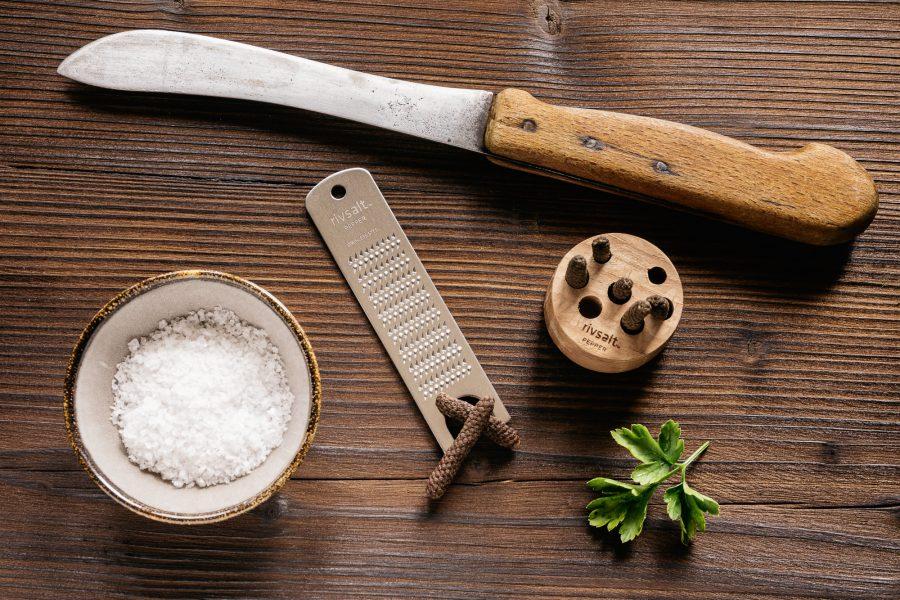 Ein Holzbrett mit einer kleinen Reibe aus Stahl für Pfeffer, daneben Pfeffer zum reiben und ein scharfes Messer, sowie grobes Meersalz.